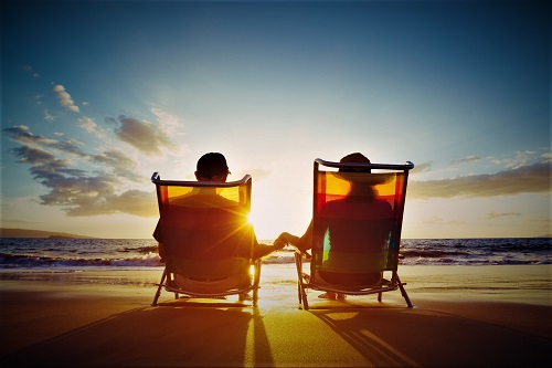 Retirement Vacation Concept, Happy Mature Retired Couple Enjoying Beautiful Sunset at the Beach